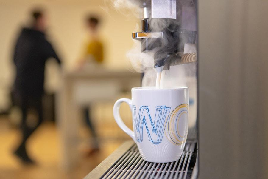 Aus einem Kaffeeautomaten läuft Kaffee in eine Tasse