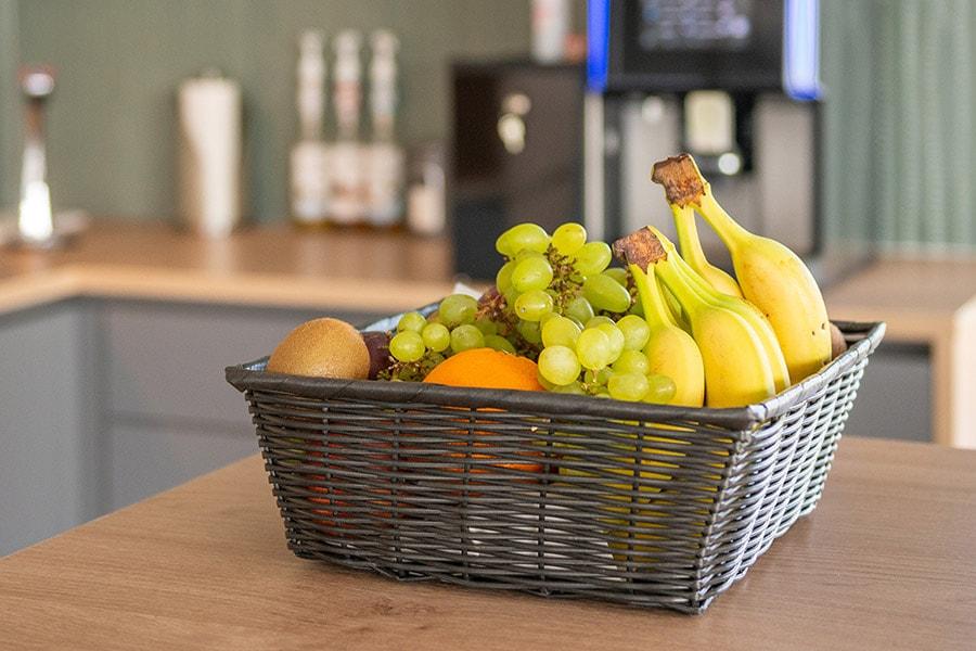 Obstkorb im Aufenthaltsraum mit Bananen, Trauben, Äpfeln, Kiwis und Orangen