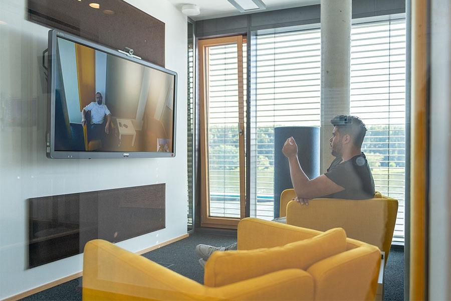 Im virtuellen Besprechungsraum sitzt ein Mitarbeiter und spricht mit einem Kollegen am zweiten Standort
