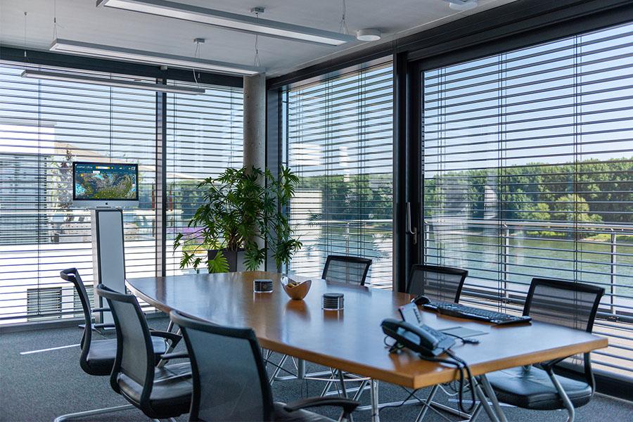 Blick in den großen Konferenzraum, der mit vielen Sitzplätzen und Blick auf den Rhein zum Arbeiten einlädt