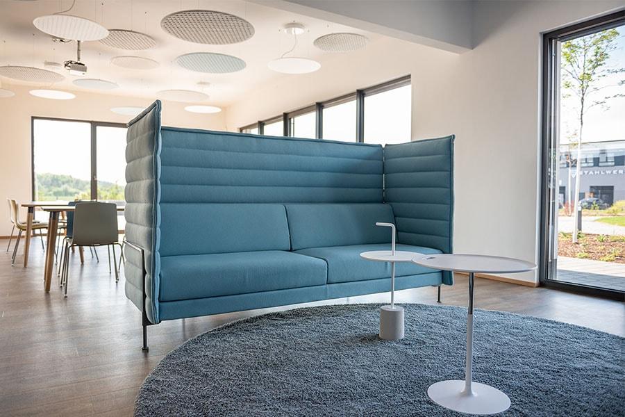 Im Aufenthaltsraum lädt ein blaues Sofa zum Verweilen ein
