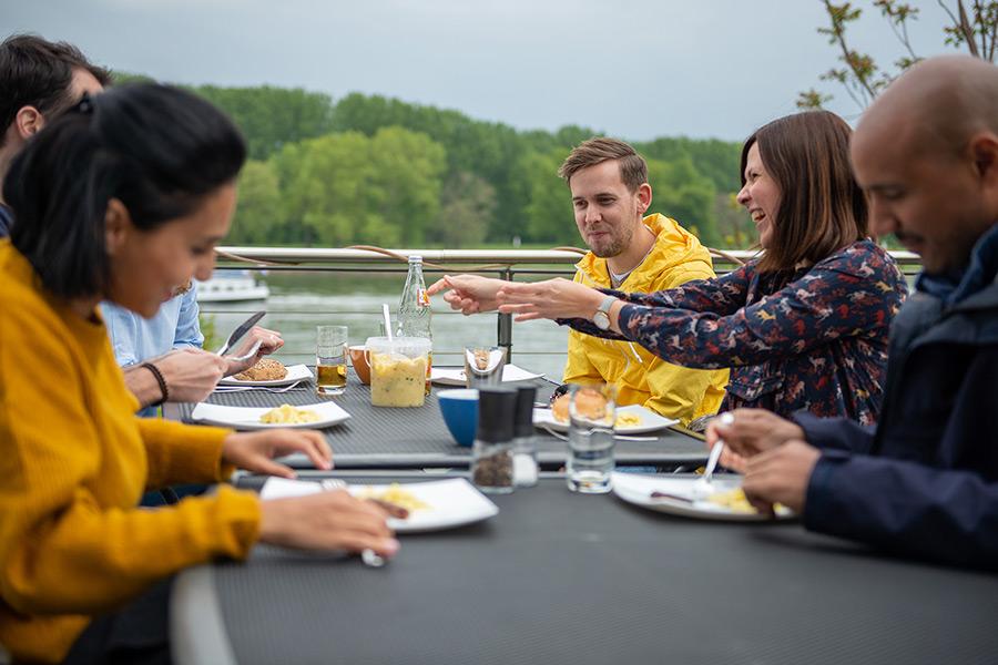 Mitarbeiter grillen und essen in der Mittagspause gemeinsam