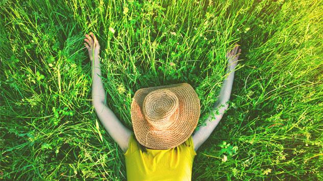 Eine Frau liegt mit Hut über dem Gesicht im grünen Gras