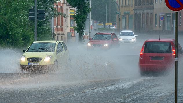 Autos fahren durch Wasser auf der Straße